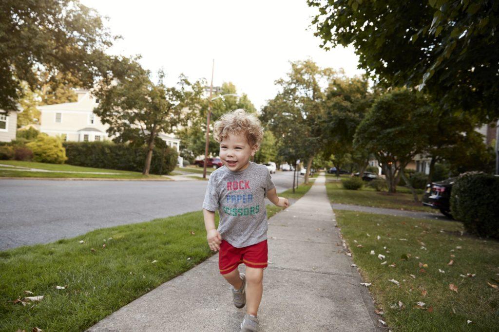 Toddler boy running in a quiet residential street